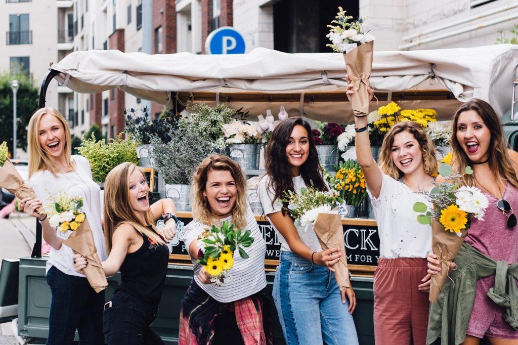 Dzień Kobiet w pracy. Zdjęcie przedstawia 6 radosnych kobiet trzymających żółte kwiaty. W tle spokojna uliczka, stragan z kwiatami.