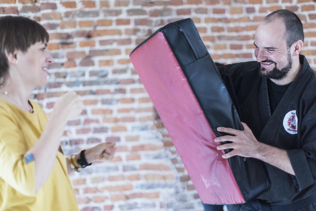 Warsztaty z samoobrony. Roześmiany instruktor samoobrony w kimonie trzyma tarczę do sztuk walki. Młoda kobieta w żółtej bluzce uderza pięścią w tarczę.